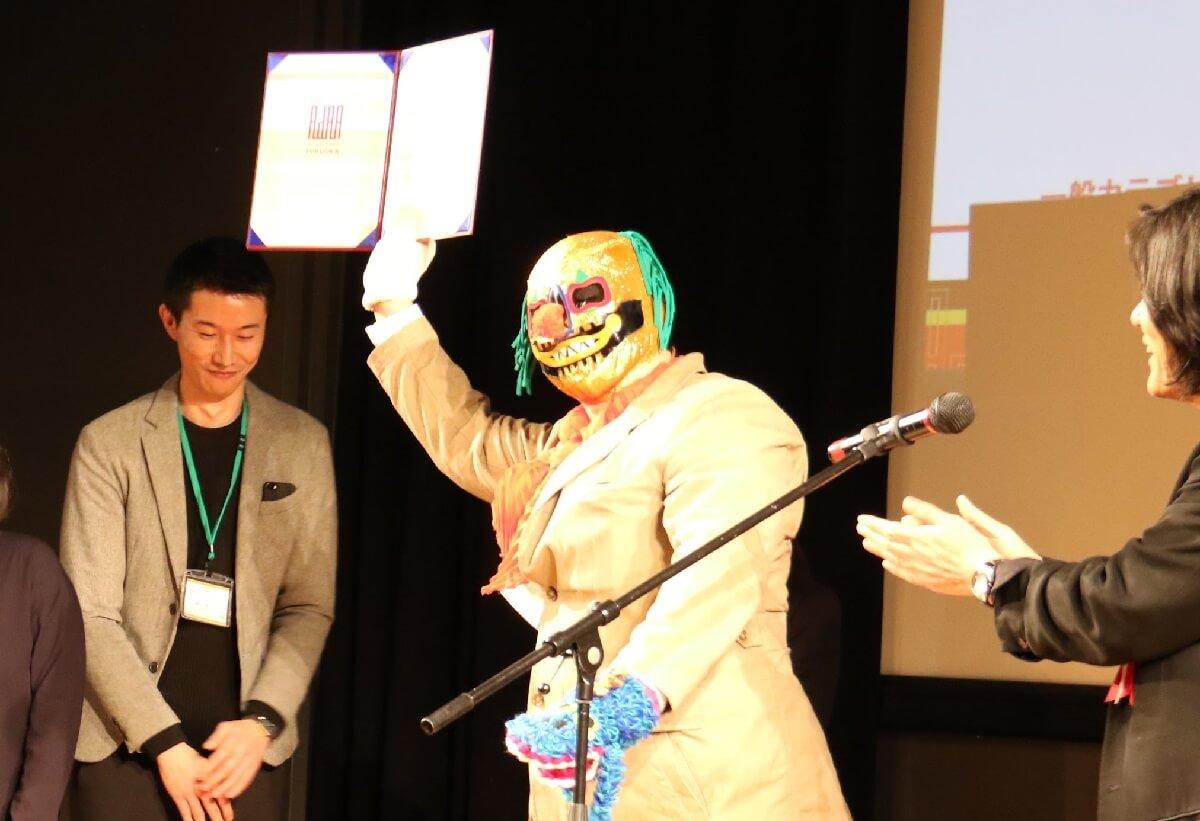 表彰式でピエロ仮面を被っているプロレスラー受賞者の写真